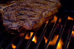Grilling a T bone steak to illustrate importance of eating less meat in heart health